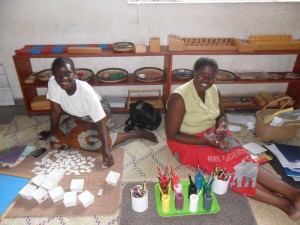 Jane Katera (teaching assistant) and Hilda Mandota (teacher for Paw Paw, 2 1/2-6 year old class) preparing the environment for learning!