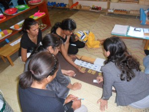 Evone Azraa leading her fellow students through a Montessori math lesson. Practice, practice, practice!